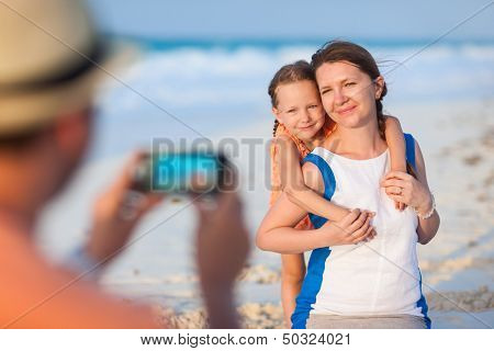 Young man making photo of his wife and daughter at tropical beach. Focus on girls