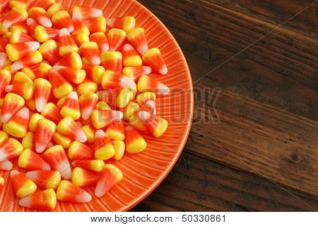 Candy corn in orange dish on rustic wood background with copy space.