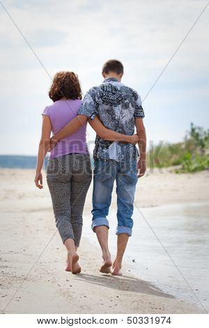Man And Woman Are Walking On The Beach