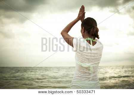 Woman doing yoga on Punta Cana beach. Vacation.