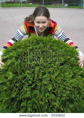 Girl Embraces Green Bush In Shape Of Ball