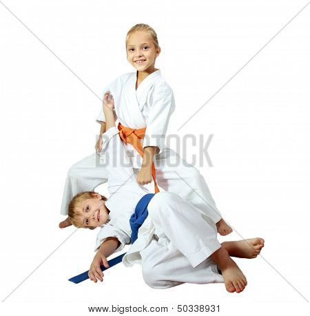Cheerful kids athletes in kimono doing throws
