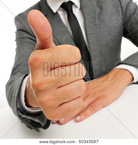 man wearing a suit sitting in a table giving a thumbs up signal