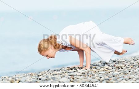 Woman In White Doing Yoga On  Beach