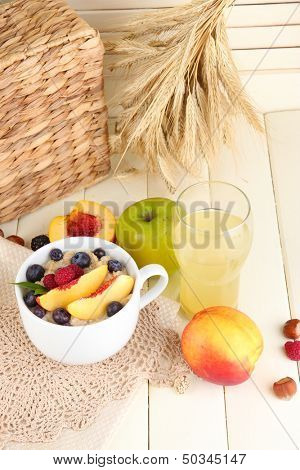 Oatmeal in cup with berries on napkins on wooden table on bright background
