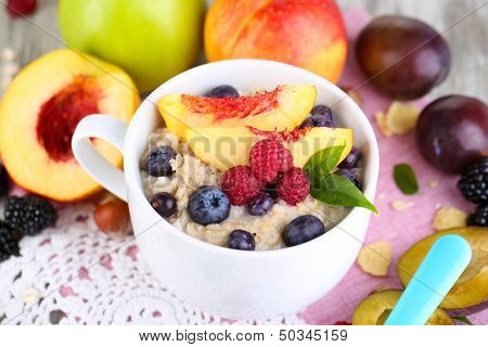 Oatmeal in cup with berries on napkins on wooden table