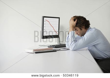Overworked businessman with head in hands sitting at desk in office