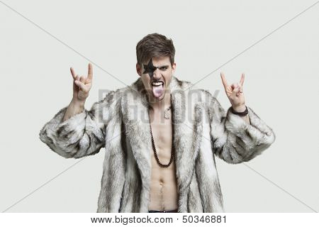Portrait of an angry young man making rebellious gestures and sticking out tongue against gray background