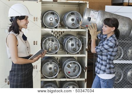 Asian woman looking at female industrial worker carrying propane cylinder