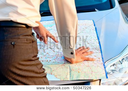 Businessman looking at a map spread out on the hood of a car