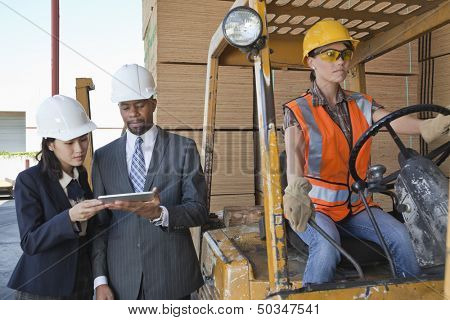 Engineers using tablet PC with female industrial worker driving forklift truck