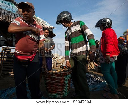 PADANG - AUGUST 25: Fishmongers carry a basketful of fish after a wholesale purchase at a village market in Padang, West Sumatera, Indonesia on August 25, 2013. Fishery is a major revenue earner.