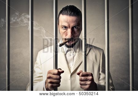 gangster locked up in a prison smokes cigar