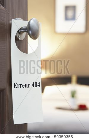 "Sign with French text ""Erreur 404"" (error 404) hanging on hotel room door"