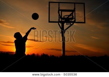 Silhouette Of Teen Boy Shooting A Basketball