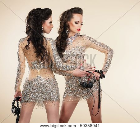 Soiree. Two Elegant Shapely Women In Grey Dresses