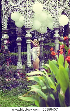 Sentiment. Beautiful Relaxed Blonde Holding Air Balloons In The Garden