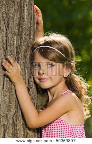 Pensive Little Girl Near A Tree