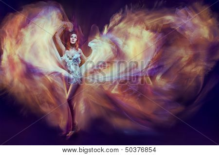 Woman In Waving Dress As A Flame Dancing With Flying Fabric. Art Dark Background