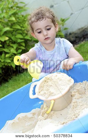 Young child playing in sand pit.