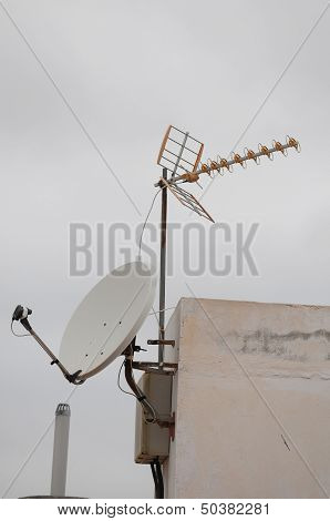 Antennas On A Roof Over A Cloudy Sky