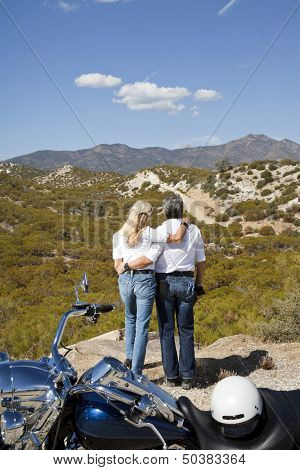 Senior couple look out to desert mountains