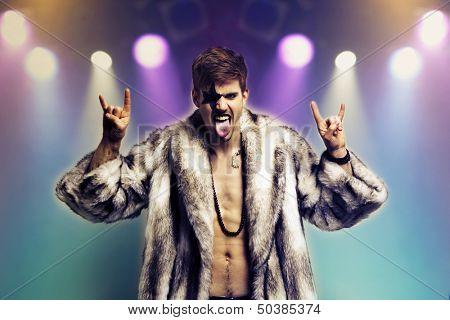 Portrait of young man in fur coat making rebellious hand gestures in rock concert