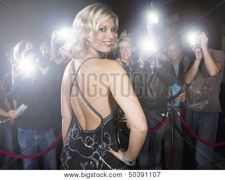 Portrait of beautiful young woman posing for paparazzi