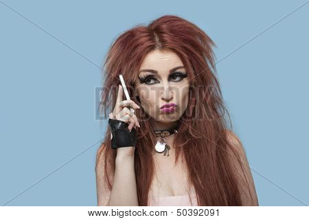 Young funky woman puckering while using cell phone over blue background