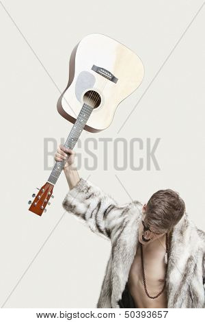Frustrated young man in fur coat about to throw his guitar against gray background