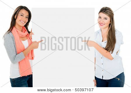 Women pointing a banner and smiling - isolated over white background