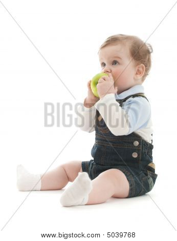 Adorable Baby Boy Sit And Eat Green Apple Over White