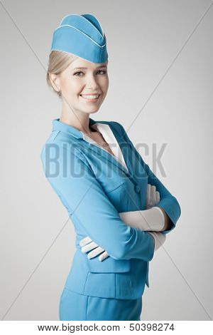 Charming Stewardess Dressed In Blue Uniform On Gray Background