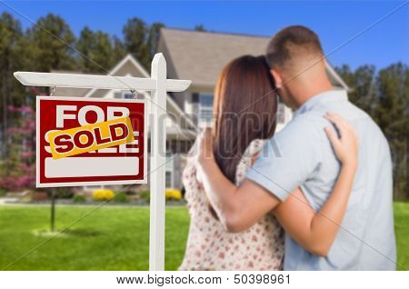 Sold For Sale Real Estate Sign and Affectionate Military Couple Looking at Nice New House.