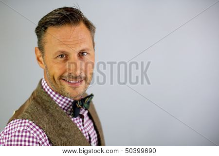 Smiling trendy guy with bowtie on white background
