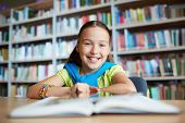 stock photo of schoolgirl  - Portrait of cheerful schoolgirl looking at camera while sitting in library - JPG