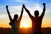 stock photo of woman  - Successful couple of young athletes raising arms to golden summer sunset sky after training - JPG