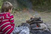 stock photo of boy scout  - outdoor portrait of young child boy looking at fire - JPG
