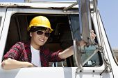 picture of logging truck  - Female industrial worker adjusting mirror while sitting in logging truck - JPG