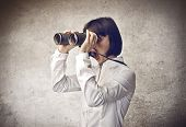 surprised young woman looking through binoculars
