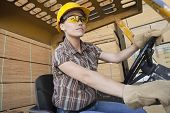 image of heavy equipment operator  - Female industrial worker driving forklift truck with stacked wooden planks in background - JPG