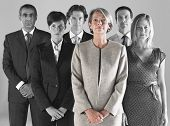 Ambitious businesswoman with team of professionals against gray background