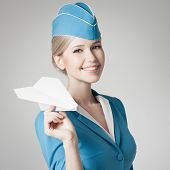 Charming Stewardess Holding Paper Plane In Hand. Gray Background.