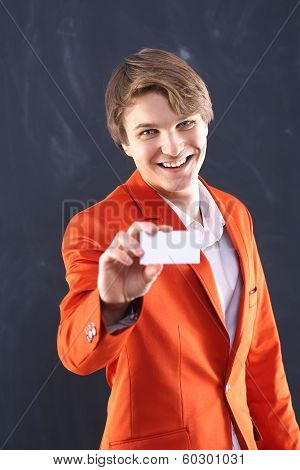 Joyful boy in orange jacket with white showcase