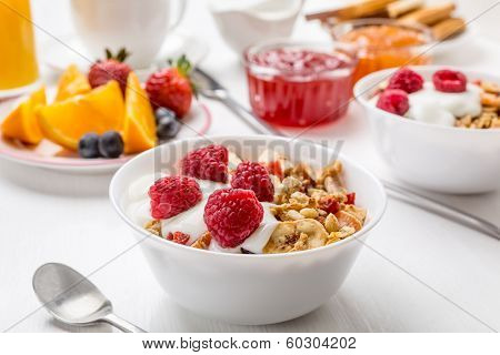 Healthy Breakfast Meal - Bowl of Fruit, Oat and Nut Granola  with Yogurt and Raspberries