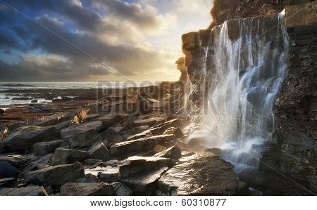 Beautiful Landscape Image Waterfall Flowing Into Rocks On Beach At Sunset