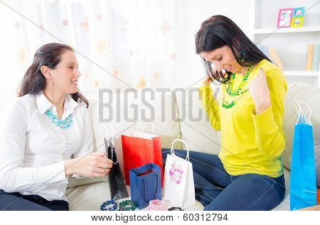 Two beautiful women friends at home with  shopping bags and jewelry