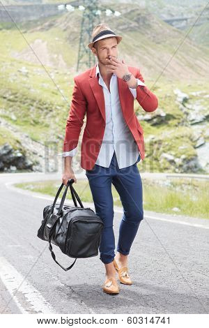 picture of a young fashion man walking on the middle of the road while holding a bag in his hand and smoking