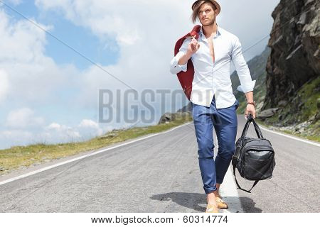 sexy young fashion man walking down the middle of a road in the mountains while holding his jacket over his shoulder and a bag in his hand and looking away from the camera
