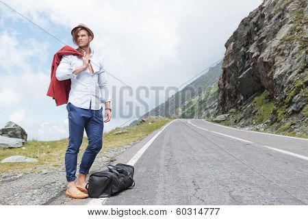 attractive young fashion man posing outdoor, on the side of the road, with his jacket over his shoulder and his bag at his feet, while looking away